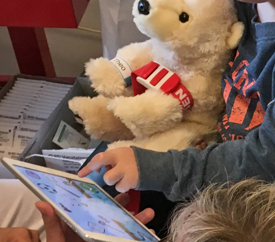 Hospitalized at Børneriget child with tablet and Theo teddybear