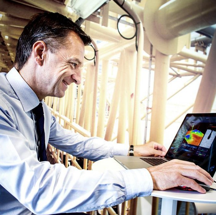 Claus V Hemmingsen CEO at Maersk Drilling sitting by a laptop at a construction ground